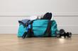 Leinwandbild Motiv Blue gym bag with sports accessories on floor near white wall indoors