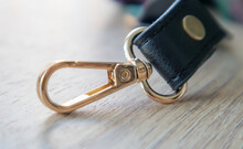Swivel Carabiner Fastener With Leather Black Bag Strap On A Wooden Background. Metal Carabiner With Swivel Clip Or Hook. Small Gold Fittings Close-up In Selective Focus.