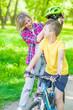 Leinwandbild Motiv Mother put on helmet to her young son for a safe ride on a bike or roller skates