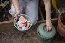Woman Putting Food Scraps In Compost Bucket