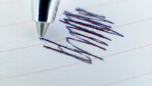 Close Up Of Metalized Ballpoint Pen Writes In Lined Notebook