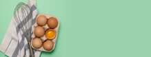 Whisk Or Egg Beater With Brown Chicken Eggs In A Eco Basket On Green Background. Diet Food