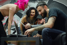 Group Of Colleagues Discussing Sketch On Computer In Tattoo Studio