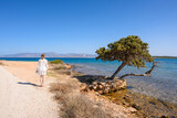 Fototapeta Kwiaty - A young woman stands on the seafront on the island of Paros. Cyclades, Greece