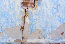 Fragment Of The Wall Of An Old Brick House. There Is A Large Crack. Remnants Of Plaster And Blue Paint Are Visible. Background. Texture.