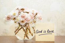 God Is Love - Christian Lettering, Biblical Phrase And Bouquet Of Pink Flowers In Vase