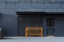 Corrugated Gray Metal Facade. Metal Movable Fence In A Bundle. Fan Barrier. Temporary Fence Against The Backdrop Of A Metallic Grey Facade. Black Glass Door