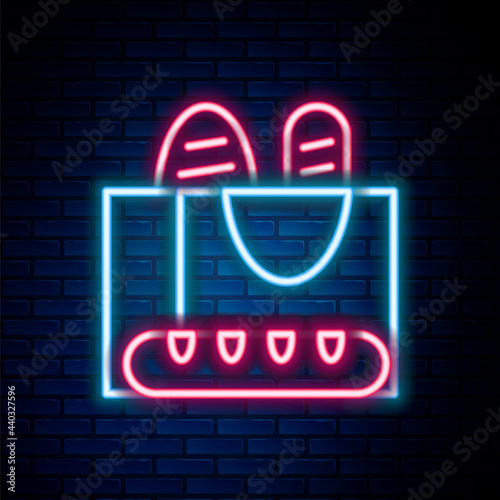 Fotografie, Obraz Glowing neon line French baguette bread icon isolated on brick wall background