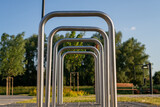 Fototapeta Fototapety do łazienki - Metalowe stojaki rowerowe w parku, zielone drzewa w tle