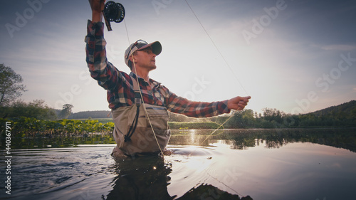 Obraz na plátně Fly fisherman stands in the water and casts the fly with fishing rod