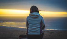 A Woman Sitting And Meditating On A Hill Staring At The Sunset Over The Ocean