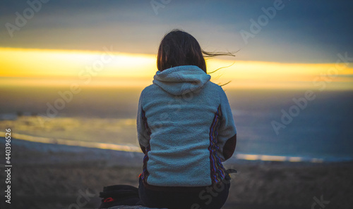 Tablou Canvas a woman sitting and meditating on a hill staring at the sunset over the ocean