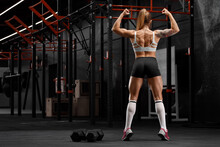 Muscular Woman Showing Back Muscles In Gym. Athletic Girl Working Out
