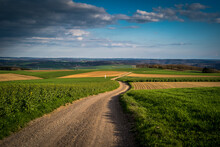 Scenic View Of A Vast Agricultural Field With A Long Road In The Countryside Under A Cloudy Sky