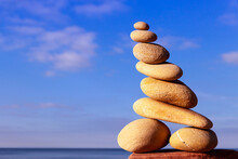 Rock Zen Pyramid Of Yellow Stones On A Beach On The Background Of The Sea. Concept Of Life Balance