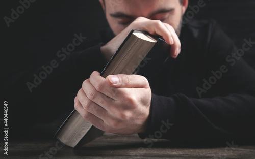 Fotografie, Obraz Caucasian man praying in the dark room.