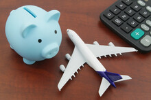 Save Money For Airplane Tickets, Planning Travel Budget Concept. Airplane Model, Piggy Bank And Calculator On Wooden Table.