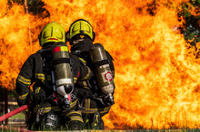 Firefighters Wearing Fire Fighter Suit For Safety And Using Twirl Water Extinguisher For Fighting The Fire Flame In Emergency Situation.. - Safety Firefighter And Industrial Concept.
