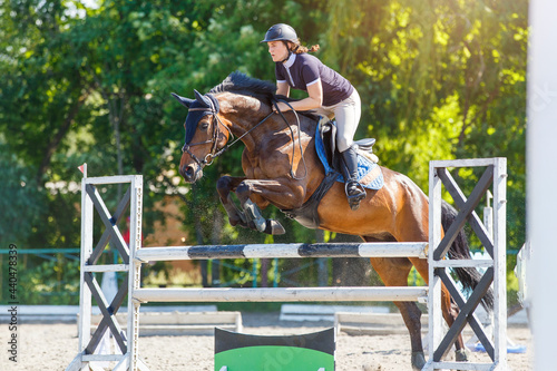 Fototapeta Young horse rider girl jumping over a barrier on show jumping course in equestri
