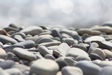 Pebble Stones On Sea Shore Blurred Out Of Focus Lights Natural Background.