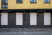 Beautiful Vintage Exterior Of Building With Old Rough Brick Wall Facade And Big Closed Wooden White Shutter Windows With Chevon Or Herringbone Pattern.