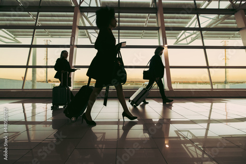 Obraz na plátně Silhouette of people walking at airport terminal
