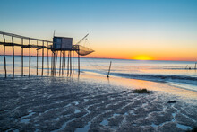 Sunset Over The Gironde Estuary During Low Tide At With Traditional Fishing Hut On Stilts In Foreground Mudflats On Coastline Of Charente Maritime, France