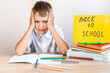 A blonde schoolboy in a white shirt sits at a desk against the background of textbooks and pencils with a yellow sign back to school