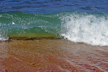 Close-up Detail Of The Crest Of A Small Clear Green Ocean Wave Breaking Onto The Beach