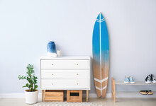 Interior Of Modern Stylish Hall With Surfboard, Shoe Stand And Chest Of Drawers