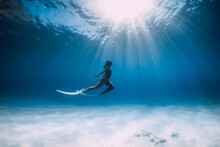 Freediver With White Fins Glides And Posing Underwater In Sea With Sunlight.