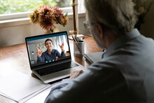Back View Of Old Caucasian Man Look At Laptop Screen Talk Speak On Video Call With Young Indian Coach Speaker. Mature Male Have Webcam Digital Chat On Computer With Trainer. Virtual Event Concept.