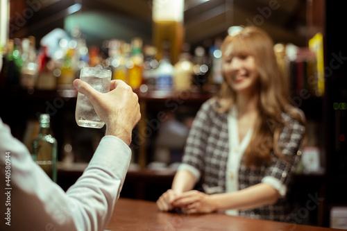 Fototapeta カウンターバーでお酒を提供する若い女性