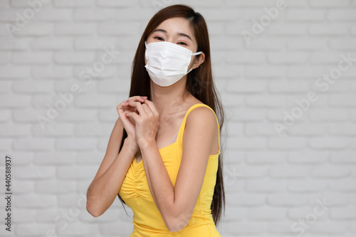 Fotografie, Obraz Wellness asian young woman wear face mask and yellow camisole holding hands prou