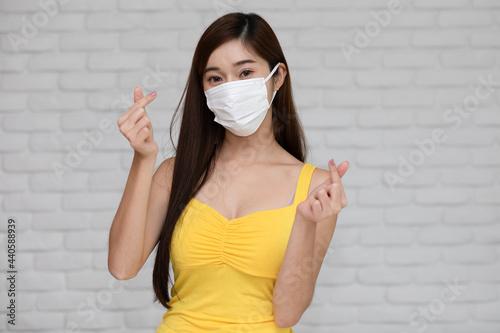 Fototapeta Wellness asian young woman wear face mask and yellow camisole make mini heart fo
