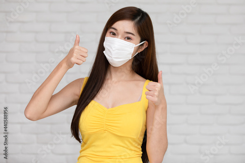 Fototapeta Wellness asian young woman wear face mask and yellow camisole thumbs up for good