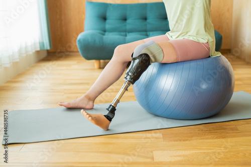 Fotografie, Obraz リビングでストレッチをする義足女性
