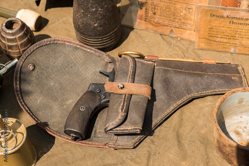 An old revolver of the Nagant system in a canvas holster lies on a demonstration Fototapeta