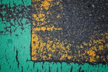 緑色と黄色い部分が古くなって不思議な模様を描いているアスファルト道路