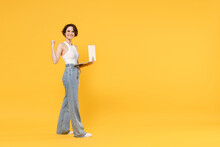 Full Length Side View Young Freelancer Fun Woman 20s Wear White Tank Top Shirt Using Laptop Pc Computer Chat Online Browsing Internet Walk Do Winner Gesture Clench Fist Isolated On Yellow Background.