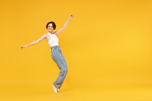 Full Length Side View Young Woman 20s With Bob Haircut Wearing White Tank Top Shirt Walking Go Stand On Toes Leaning Back Fooling Around Dancing Isolated On Yellow Background People Lifestyle Concept.