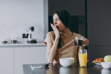 Young Tired Sleepy Housewife Woman 20s In Casual Beige T-shirt Eat Breakfast Hold Cup Of Tea Drink Coffee Yawning Cover Mouth Cook Food In Light Kitchen At Home Alone Healthy Diet Lifestyle Concept.