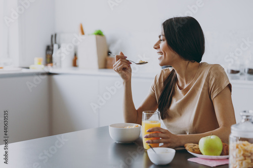 Fotografia Side view young happy smiling housewife woman 20s wearing casual clothes beige shirt eat oatmeal porridge muesli in morning cooking food in light kitchen at home alone