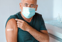 Male Senior In Face Mask After Receiving COVID-19 Vaccine. Elderly Man Feeling Good On Getting Coronavirus Vaccine. Covid Vaccination For Older People. Senior Patient Showing Arm With Bandage, Patch