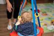Ein kleines Baby sitzt in dem Schaukel, in seinem Zimmer, Der Kleine hat blonde Locken. Über all liegen Spielsachen rum. Vor ihm steht seine Mutter oder seine Oma. Der Junge hält sich am Schaukel fest