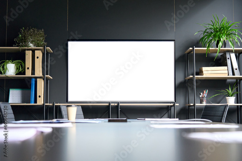 Valokuvatapetti Meeting conference room with blank empty mockup tv screen monitor for advertising standing in modern contemporary office on black wall background