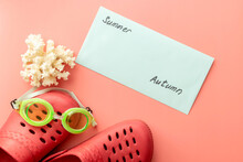 Summer Background Of Crocs, Coral, Swimming Goggles, Shells, An Envelope With The Inscription Summer, Autumn On Pink Background