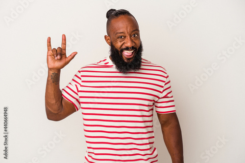Obraz na plátne African american man with beard isolated on pink background showing a horns gesture as a revolution concept