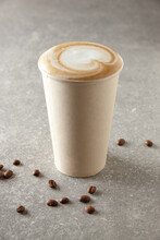 Paper Coffee Cup And Coffee Beans On Table