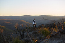 Man Standing Looking Out Over Mountains On Sunset